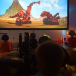 Kids chilling on bean bags screening #DreamworksDinotrux with headphones. #StreamTeam